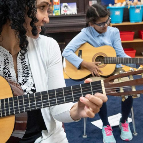Teacher and student playing the guitar